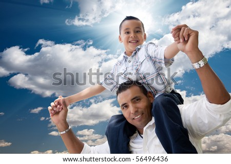 Hispanic Father and Son Having Fun Over Clouds and Blue Sky with Sun Rays. - stock photo