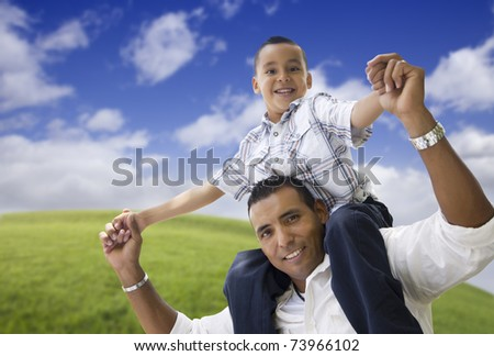 Hispanic Father and Son Having Fun Together in the Park. - stock photo