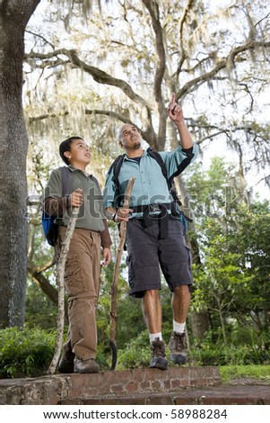Hispanic father and son hiking in park enjoying nature - stock photo