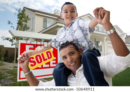 Hispanic Father and Son in Front of Their New Home with Sold Home For Sale Real Estate Sign. - stock photo