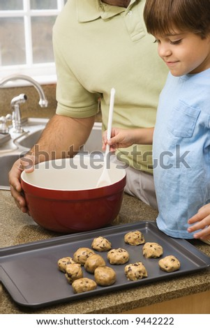 Hispanic father and son in kitchen making cookies. - stock photo