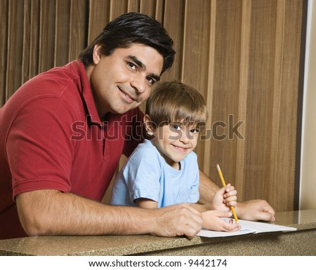 Hispanic father and son smiling at viewer with homework. - stock photo