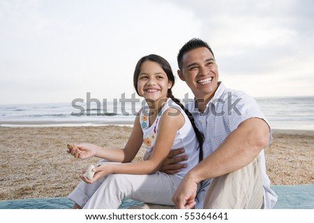 Hispanic father and 9 year old daughter having fun at beach - stock photo