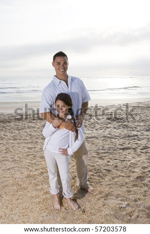 Hispanic father and 9 year old daughter standing together on beach - stock photo