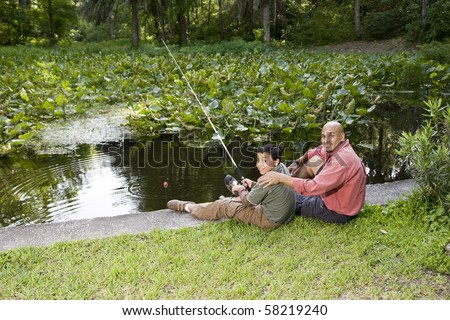 Hispanic father and 10 year old son fishing in pond