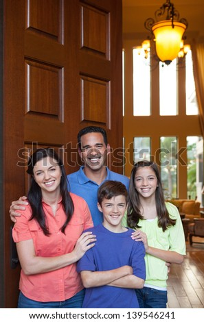 Hispanic father, Caucasian mother and mixed ethnicity son and daughter standing in entryway beside large wooden door of large home, living room with tall windows in background - stock photo