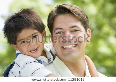 Hispanic father giving son piggy back - stock photo