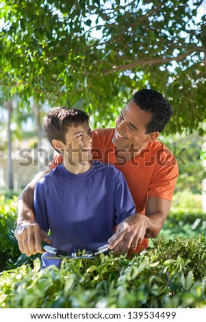 Hispanic father happily teaches his teenage son how to use hedge clippers to trim bushes in lush yard.