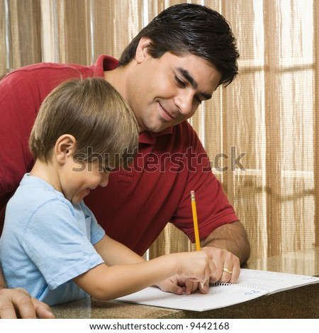 Hispanic father helping son with homework. - stock photo