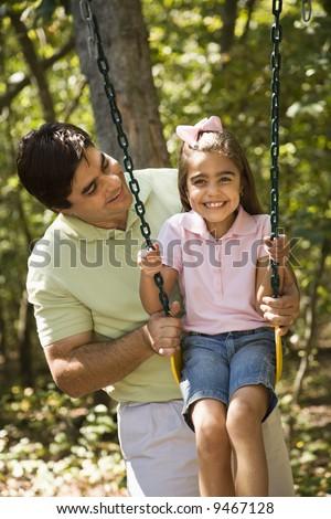 Hispanic father pushing daughter on swing. - stock photo
