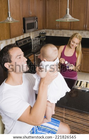 Hispanic father smiling at baby