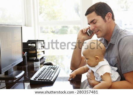 Hispanic father with baby working in home office - stock photo