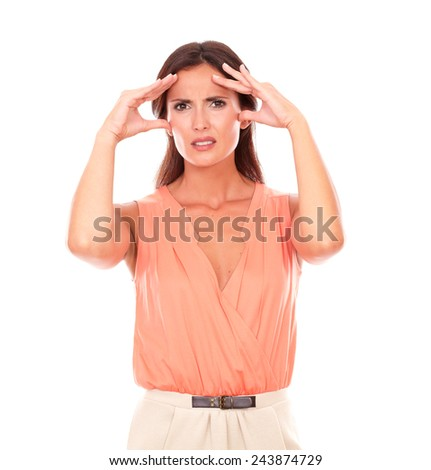 Hispanic female suffering from migraine headache with hand on head and looking at you in white background