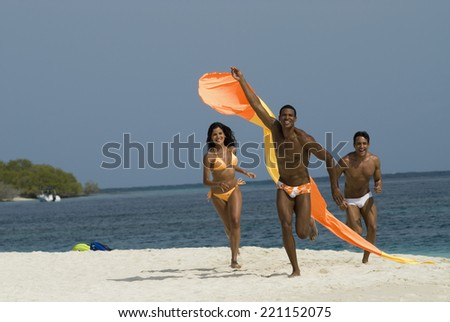 Hispanic friends flying kite at beach