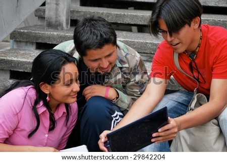 Hispanic friends looking at a computer together - stock photo