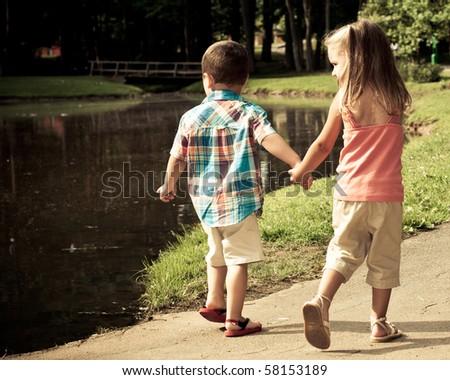 Hispanic girl and boy walk around pond. - stock photo