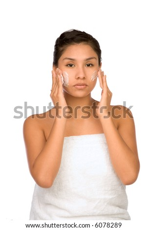 Hispanic girl applying facial skincare product - stock photo