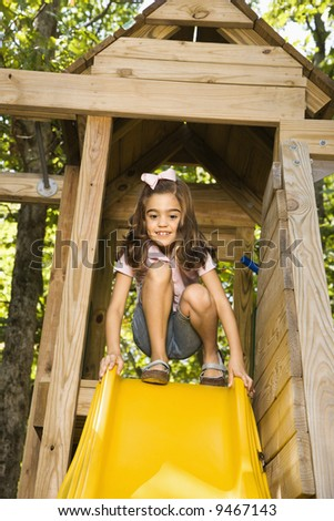 Hispanic girl crouching on top of slide smiling. - stock photo
