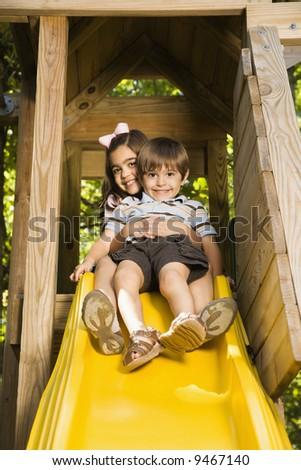 Hispanic girl hugging boy on top of slide smiling at viewer. - stock photo