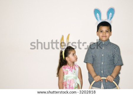 Hispanic girl looking up at Hispanic boy holding Easter basket both wearing bunny ears. - stock photo