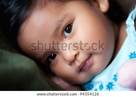 Hispanic girl resting her head on a pillow, with a subtle smile - stock photo