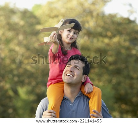 Hispanic girl sitting on father's shoulders - stock photo