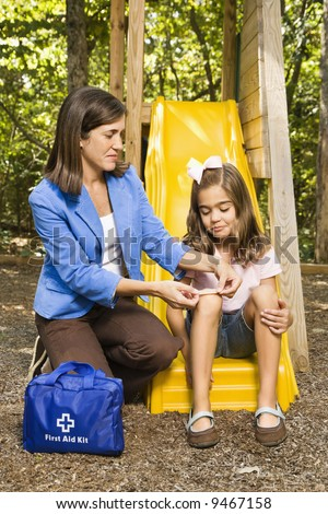 Hispanic girl sitting on playground slide while woman applies first aid bandage to knee. - stock photo