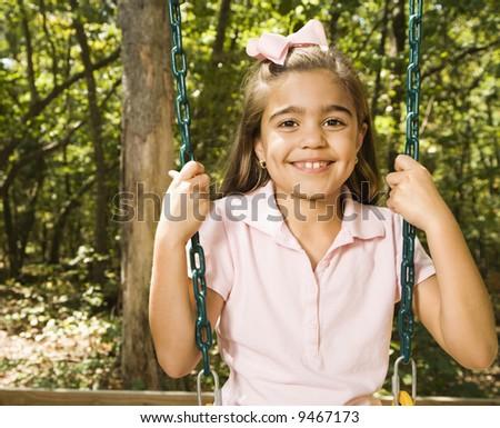Hispanic girl sitting on playground swing smiling at viewer. - stock photo