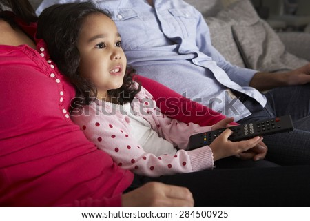 Hispanic Girl Sitting On Sofa And Watching TV With Parents - stock photo
