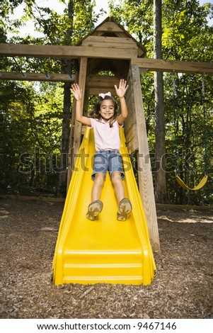 Hispanic girl sliding down outdoor slide with arms raised above head. - stock photo