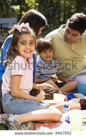 Hispanic girl smiling at viewer with family picnicing in the park. - stock photo