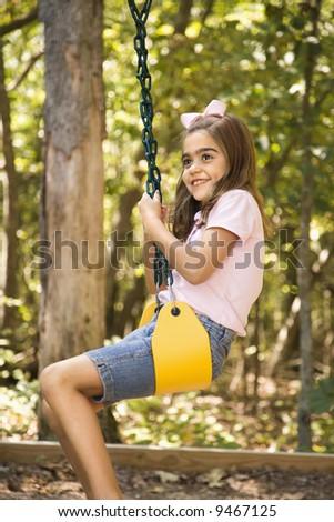 Hispanic girl swinging and smiling. - stock photo