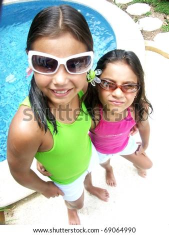 Hispanic girl with sunglasses enjoying a swimming pool. - stock photo