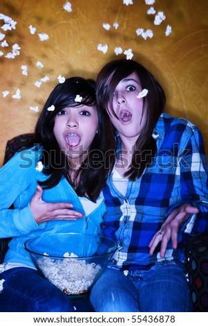 Hispanic girls with popcorn watching television - stock photo