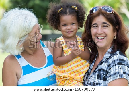 Hispanic grandma, mother and small daughter in a park - stock photo