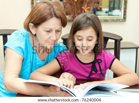 Hispanic grandmother and granddaughter reading an illustrated  book - stock photo