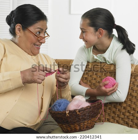 Hispanic grandmother and granddaughter with knitting supplies - stock photo