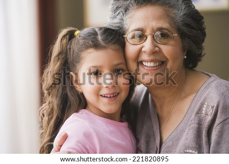 Hispanic grandmother hugging granddaughter - stock photo