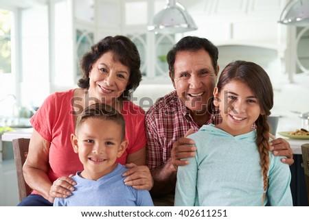 Hispanic Grandparents At Home With Grandchildren - stock photo