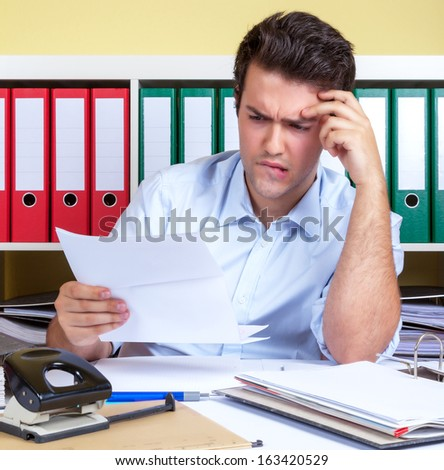 Hispanic guy with problems at office - stock photo