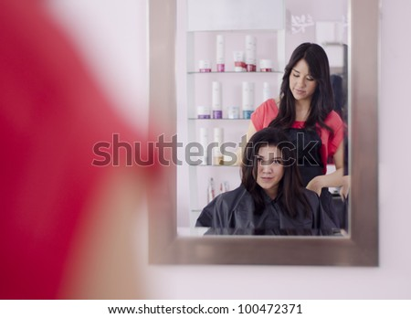 Hispanic hairdresser and client looking at hair through the mirror - stock photo