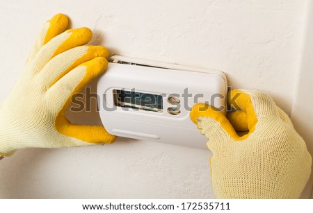 Hispanic handyman repairman conducting residential HVAC repair