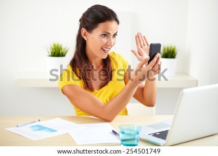 Hispanic lady taking a selfie with her cellphone in a business room