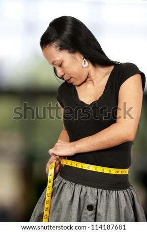 Hispanic Latino woman measuring her waist with a tailors tape - stock photo