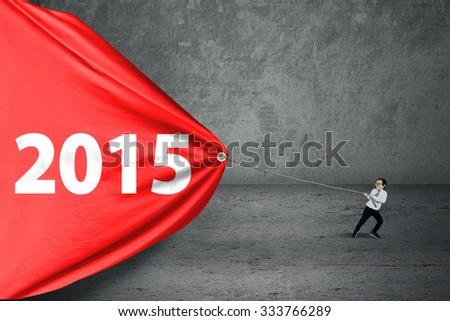 Hispanic little boy pulling number 2015 on a big banner, symbolizing an effort for progress - stock photo