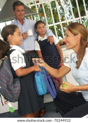Hispanic little girls going to school. Hispanic family at kitchen. - stock photo