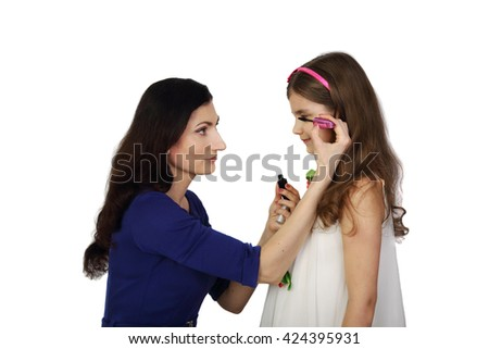 Hispanic looking woman paints girl eyelashes with mascara isolated on white background in square - Mother and daughter make up - stock photo