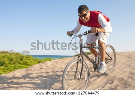 Hispanic male with mountain bike holding bottle of water with copy space - stock photo