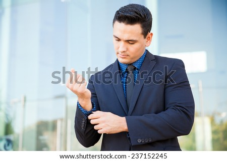 Hispanic man in a suit buttoning his sleeve and fixing up his suit before a business presentation