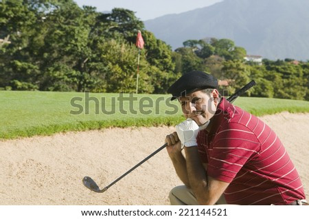 Hispanic man in golf course sand trap - stock photo